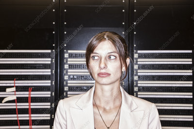 Female technician working in a large server room
