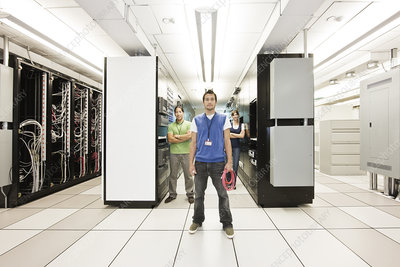 Three technicians who work in a large server room