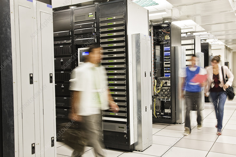 Three technicians working in a large server room
