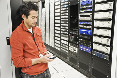 Technician on a cell phone in a large server room
