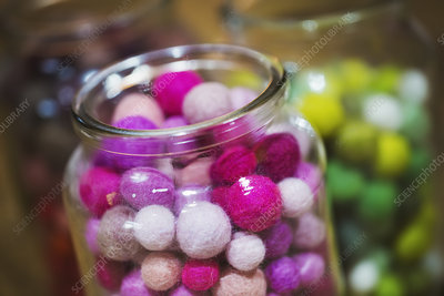 Glass jars of colourful small fabric balls