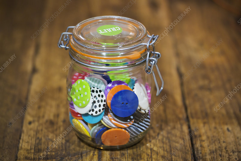 A glass jar and lid full of colourful buttons