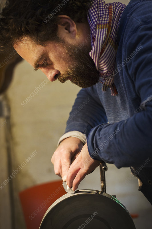 Craftsman in a workshop sharpening a knife blade