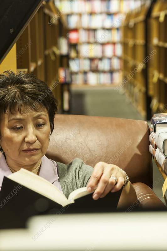 Woman browsing through books in a chair