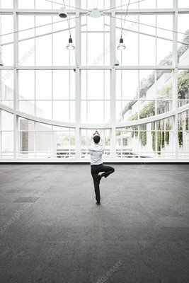 Businessman relaxing holding a yoga pose