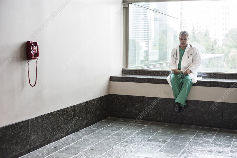 Middle Eastern man doctor texting on a cell phone