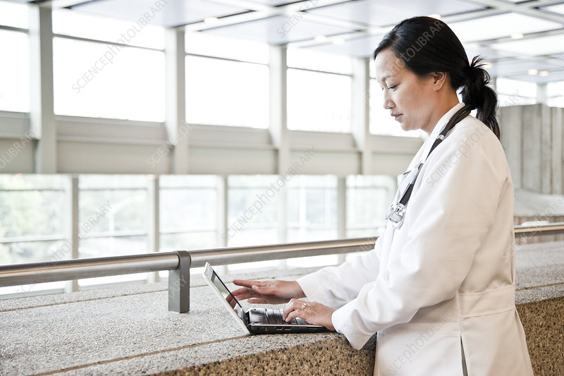 Asian woman doctor working on a laptop