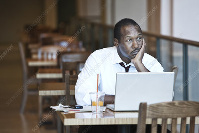 Black business man using laptop in coffee shop