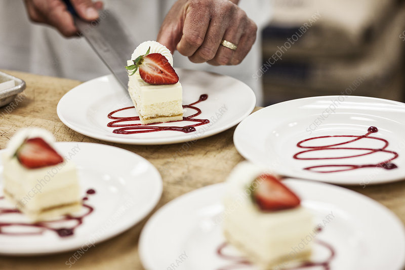 Chef hands placing a layered desert on a plate