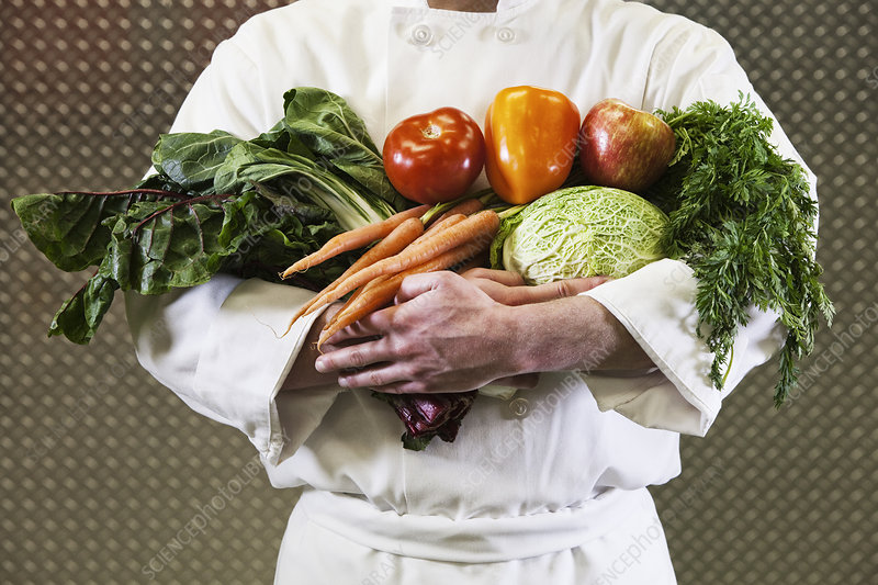 Chef with his arms full of vegetables