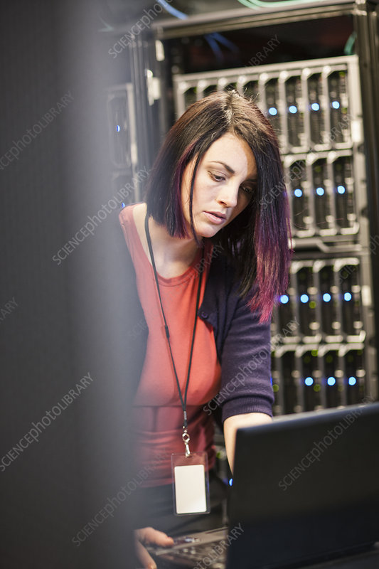 Caucasian woman technician in a large server farm