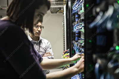 Technicians working on cables in a server farm