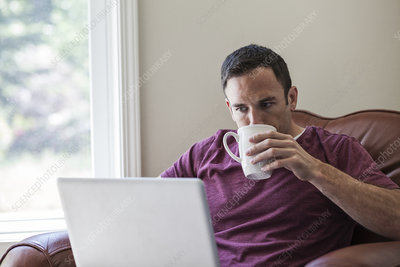 Caucasian business man using a laptop, at home