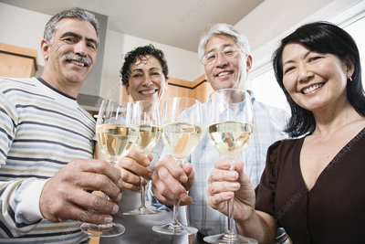 Two couples in a kitchen toasting