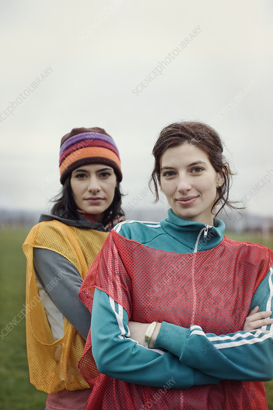 Two women in sports clothing with team bibs