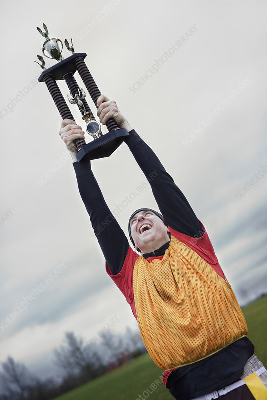 Man celebrating a sporting event win with a trophy