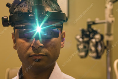 Ophthalmologist wearing an ophthalmoscope