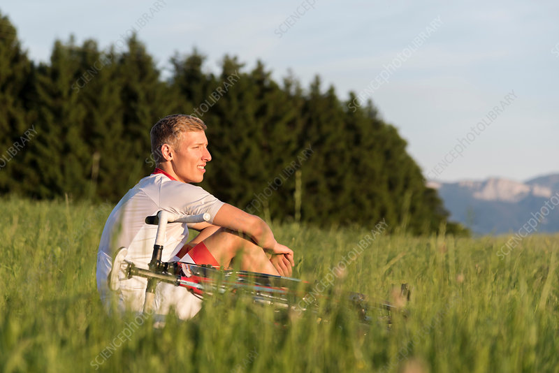 Young male cyclist sitting in field looking out