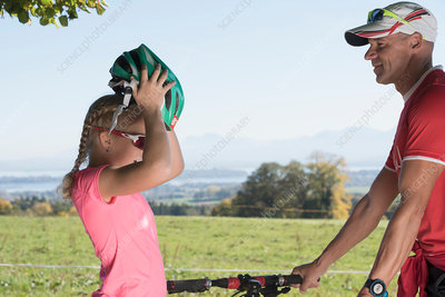 Father watching girl cyclist putting on bicycle helmet