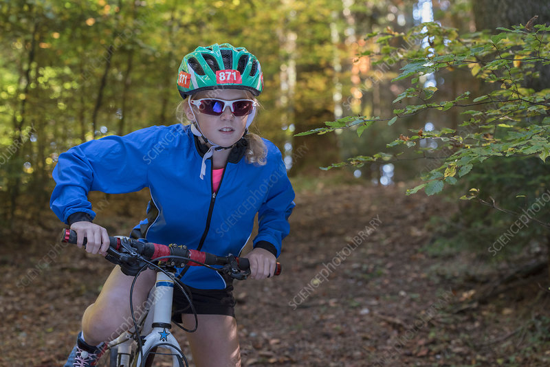 Girl mountain biker preparing to cycle in woodland
