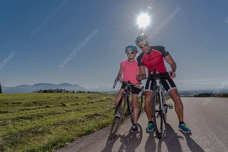 Portrait of girl and father cyclists on sunlit rural road