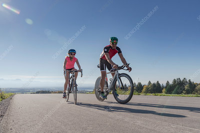 Girl and father cyclists cycling on rural road