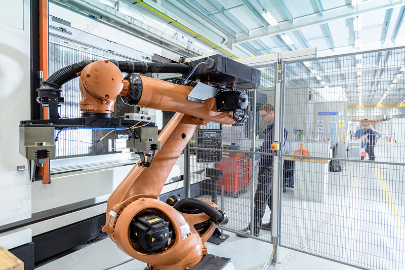 Robotics engineer operating robot aided CNC machine