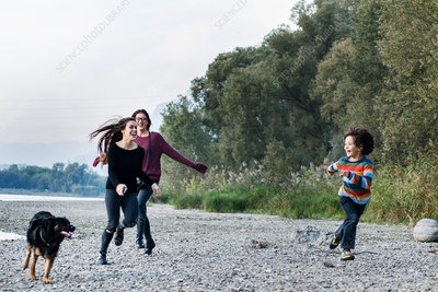 Boy and women running with dog along riverside, Italy