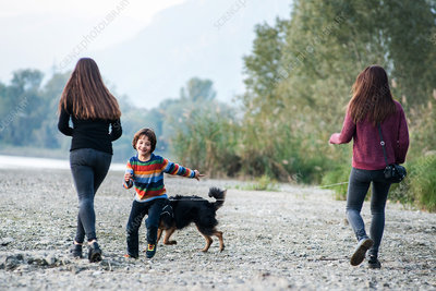 Boy with women running with dog along riverside, Italy