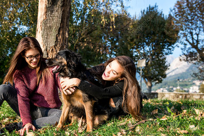 Two women hugging dog, Italy