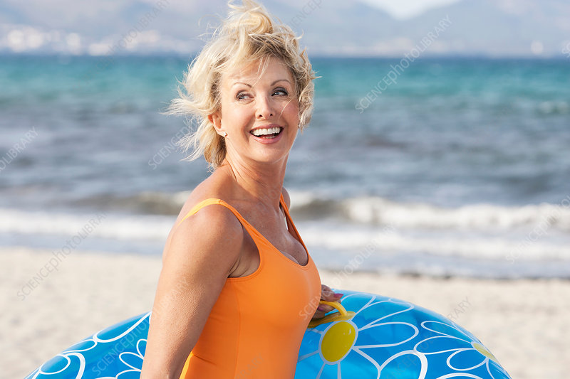Senior woman carrying inflatable on beach, Spain