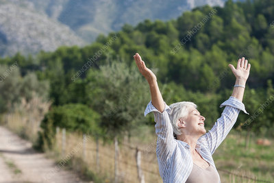 Senior woman, outdoors, arms raised, carefree expression