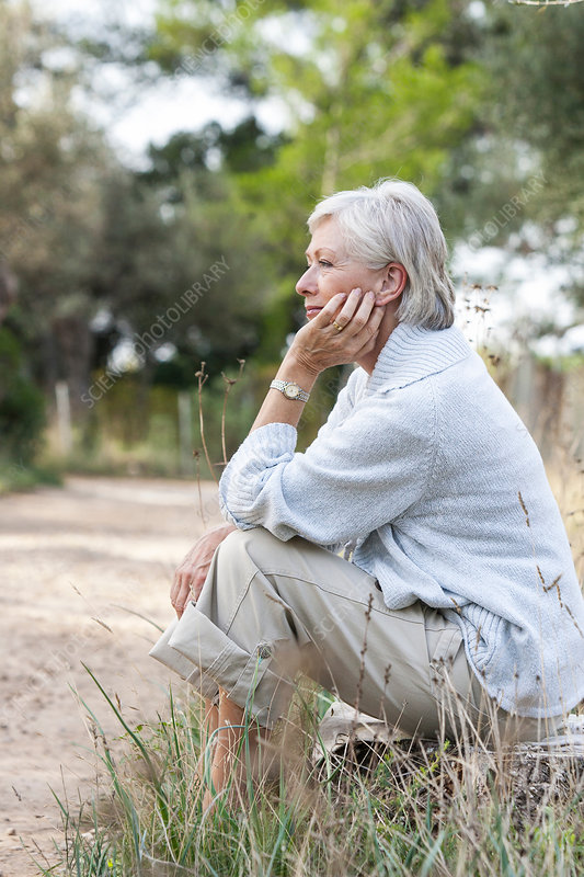 Senior woman sitting in rural setting