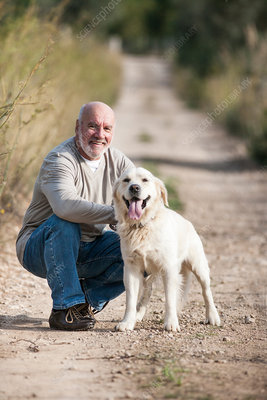 Portrait of senior man crouching beside pet dog