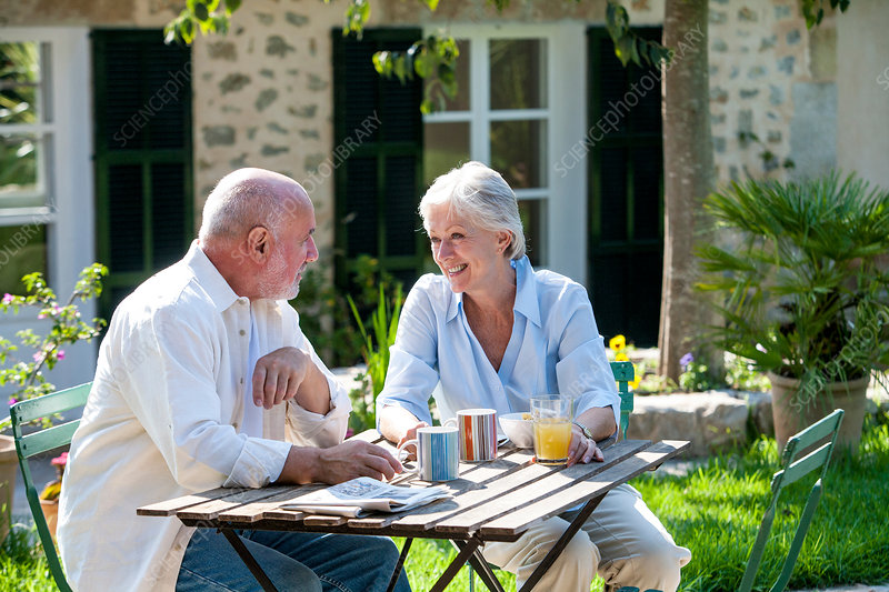 Senior couple sitting in garden, coffee cups on table