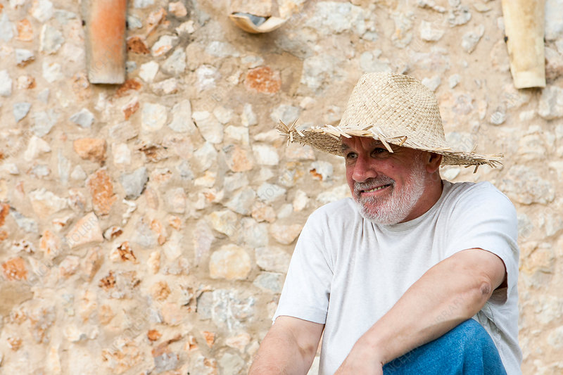 Portrait of senior man, outdoors, wearing straw hat