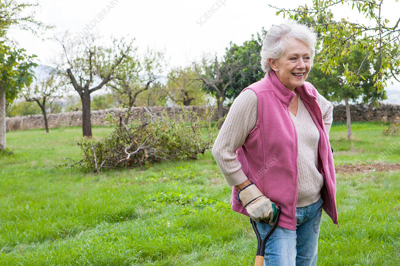 Senior woman in garden, leaning on gardening tool