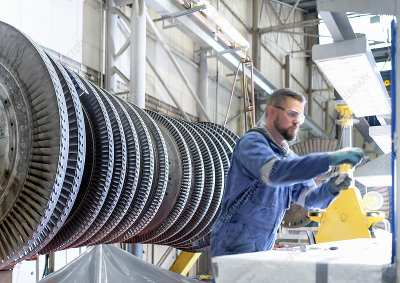 Engineer at workstation with high pressure steam turbine