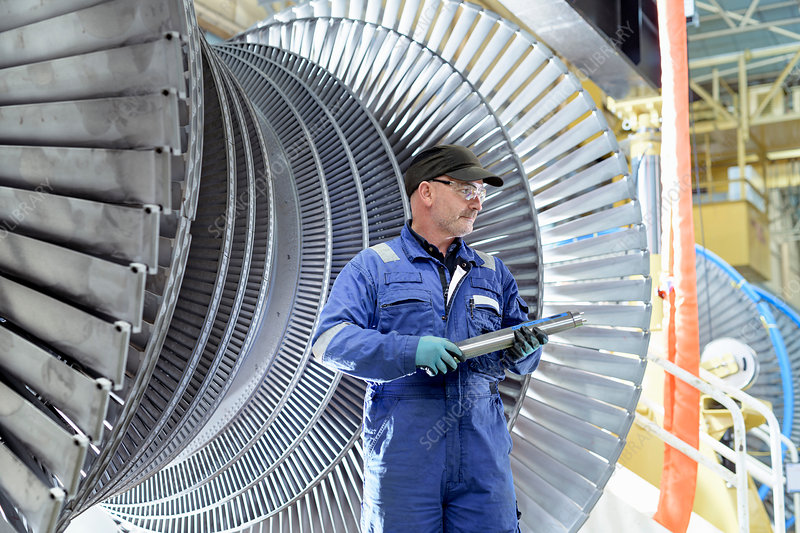 Engineer with turbine blade in turbine maintenance factory