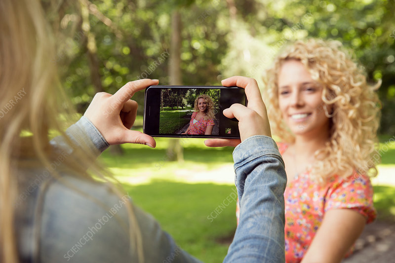 Woman taking photograph of friend using smartphone