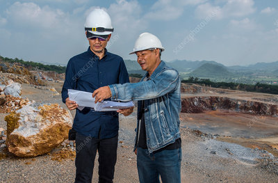 Two workers at gravel mine, discussing plans, Asia