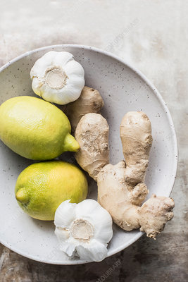 Ginger roots with lemon and garlic in ceramic bowl