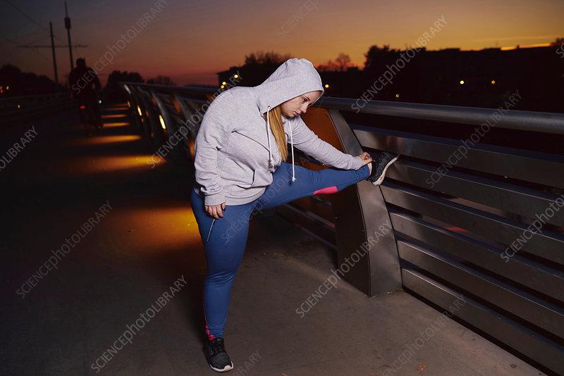 Woman training, touching toes on footbridge at night