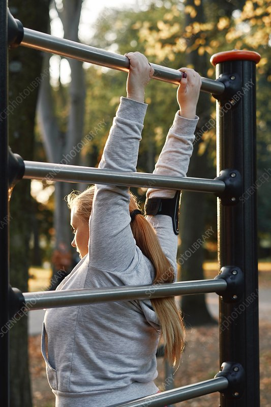 Curvaceous woman training, gripping exercise bar in park