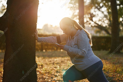 Woman training in park, doing tree trunk push ups