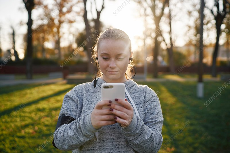 Young woman training in park looking at smartphone