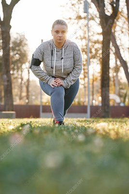 Woman training in park, leaning forward and crouching