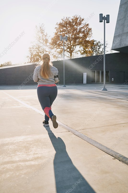 Curvaceous young female runner running, rear view