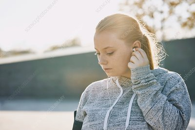 Young woman training, inserting earphones