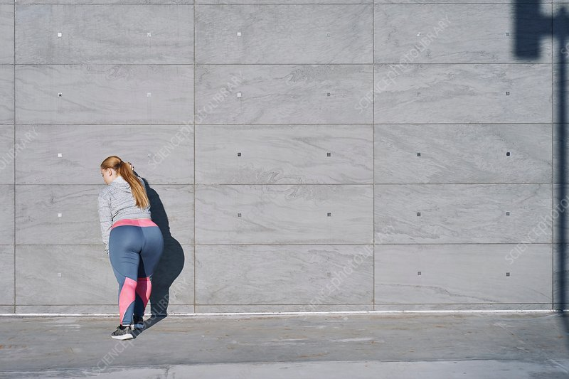 Curvaceous young woman training, doing wall push ups
